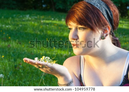 A beautiful young girl lying on the grass with some Daisys in her hand on a background of green - stock photo