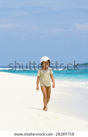 A beautiful young girl walking on the ocean beach in Maldives - stock photo