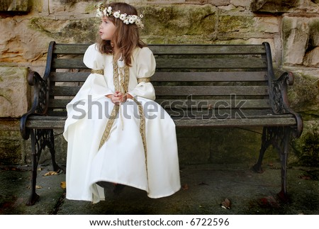 A beautiful young girl wearing a princess dress sitting on a bench - stock photo