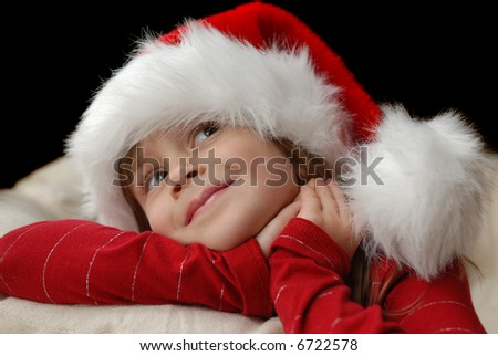 A beautiful young girl wearing a santa hat thinking about christmas - stock photo