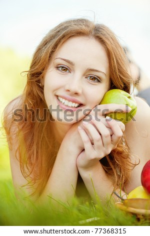 A beautiful young girl with an apple lying on the grass on a background of green nature