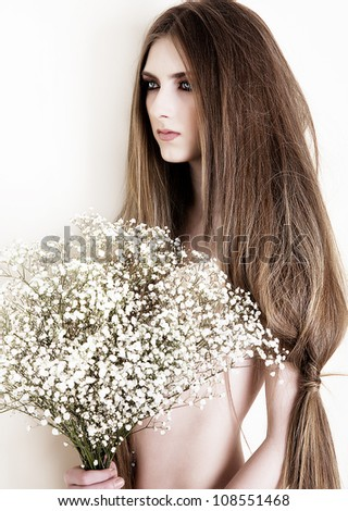 a beautiful young girl with long hair with a bouquet of flowers - stock photo