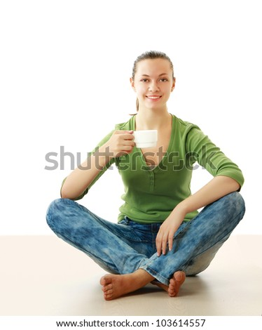 A beautiful young healthy sitting on the floor with a cup of tea or coffee smiling.