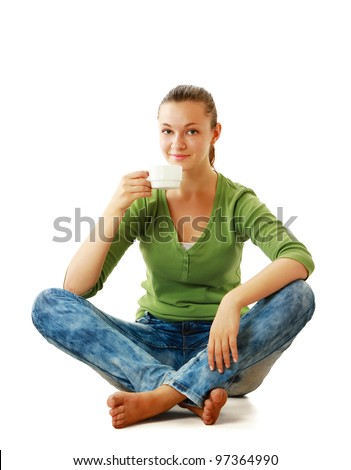 A beautiful young healthy sitting on the floor with a cup of tea or coffee smiling. isolated on white background