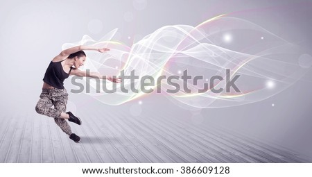 A beautiful young hip hop dancer dancing contemporary urban street dance in front of grey wall background with smokey lines and glitter concept. - stock photo