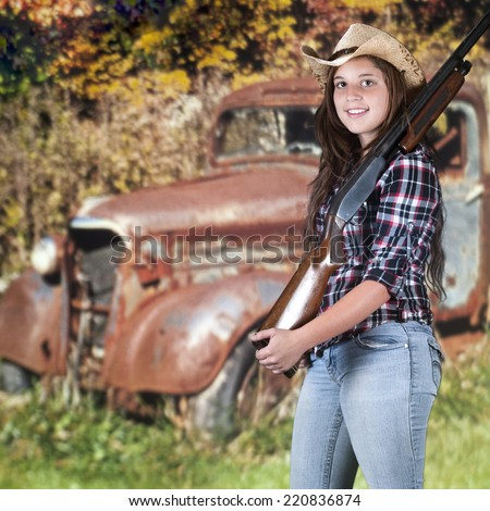 A beautiful young hunter with her rifle heading out to the woods past a rusty old truck. - stock photo