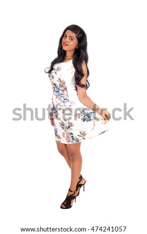 A beautiful young Indian woman standing in a summer dress with long