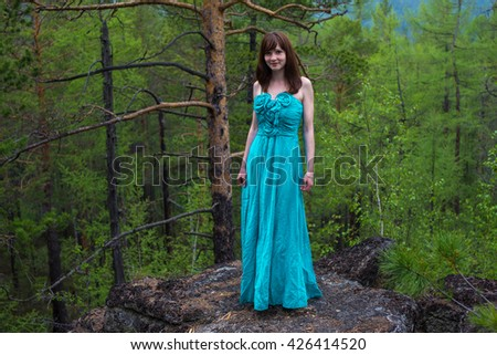 A beautiful young lady in a dress on a rock in a dreamy dark forest - stock photo
