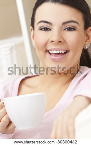 A beautiful young Latina Hispanic woman or girl with a wonderful enigmatic smile drinking tea or coffee from a white cup