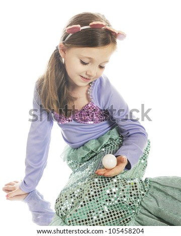 A beautiful young mermaid admiring a large pearl.  On a white background. - stock photo