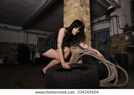 A beautiful young model in a car service. She is picking up a dirty wheel while holding a rope in the other hand.