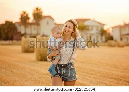 A beautiful young mother blonde in denim shorts holding a small boy son and smiles happily at sunset summer amid haystacks - stock photo