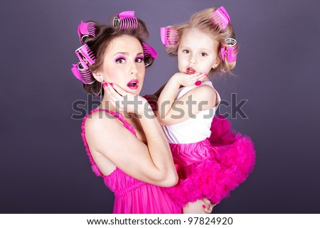 A beautiful young mother with her daughter in the form of cheerful housewives. Studio shot on a gray background. Series - stock photo
