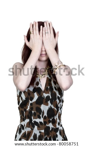 A beautiful young scared or surprised woman looking through her hands - stock photo