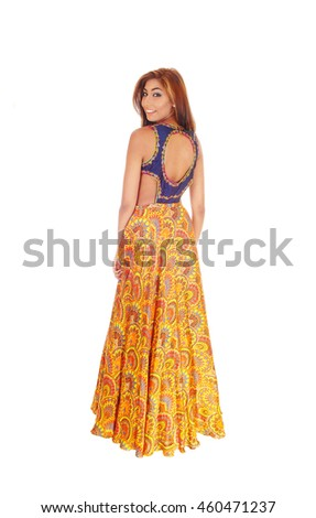 A beautiful young slim woman in a long yellow skirt standing in full length