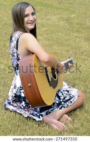 A beautiful young teen girl outdoors with a guitar. - stock photo