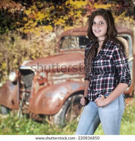 A beautiful young teen standing near a rusty, old truck near an autumn woods. - stock photo