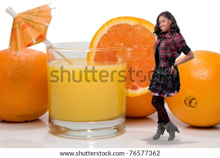 A beautiful young teenage African American woman with a glass of orange juice with an umbrella and slice. - stock photo