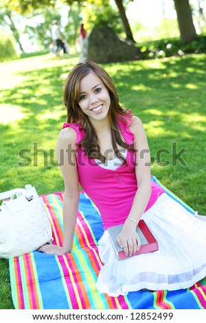 A beautiful young teenage girl in the park with a book