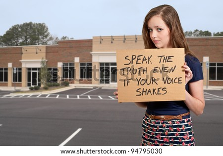 A beautiful young teenage woman holding up a sign - stock photo