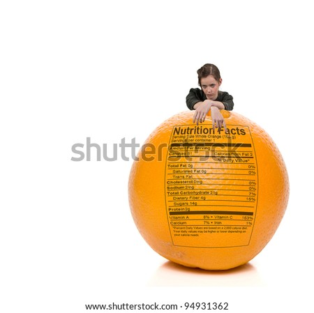 A beautiful young teenage woman standing behind an orange with a nutrition label - stock photo