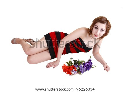 A beautiful young teenager lying on her site on the floor in a red and black striped dress, whit some flowers in front of her, for white background. - stock photo