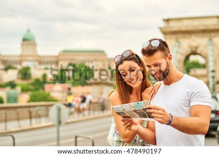 A beautiful young tourist couple are looking at a map with the castle of Buda and the Chain Bridge behind them in Budapest, Hungary.