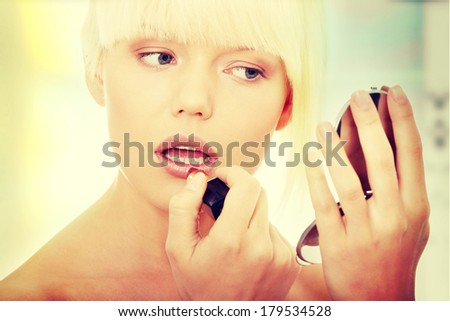 A beautiful young woman applying her make-up in the mirror  - stock photo