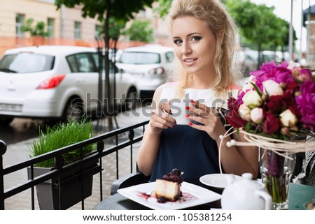 A beautiful young woman are drinking tea. Holding a cup of coffee. Outdoors