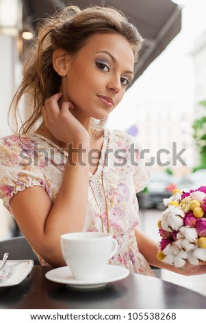 A beautiful young woman are sitting in a cafe and drinking tea. Outdoors