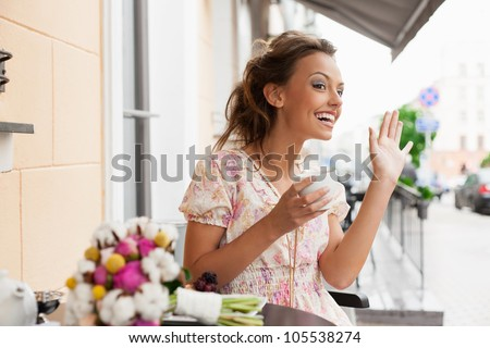 A beautiful young woman are welcoming a friend. Holding a cup of tea. Outdoors - stock photo