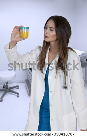 A beautiful young woman doctor holding a urine sample
