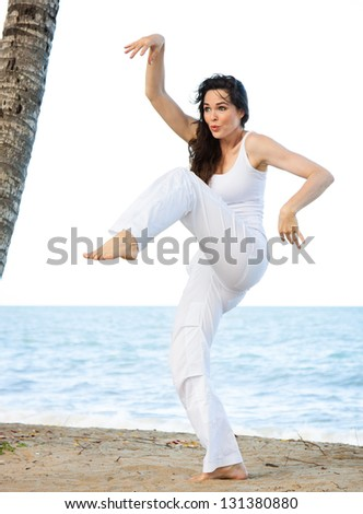 A beautiful young woman doing a silly and funny yoga pose on a beach. - stock photo