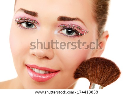 A beautiful young woman doing make-up - stock photo