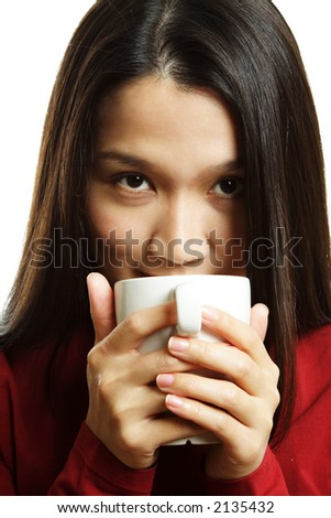 A beautiful young woman drinking a hot cup of coffee