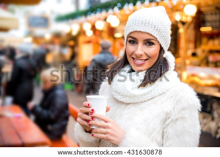 A beautiful young woman enjoying a cup of mulled wine on the christmas market. - stock photo
