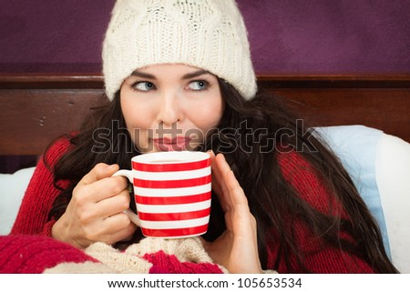 A beautiful young woman enjoying a hot drink under the blankets in bed. - stock photo