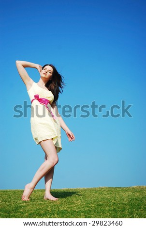 A beautiful young woman enjoying the sun outdoors in a field with a blue sky.