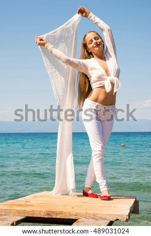 A beautiful young woman enjoying the wind and climate in the summer at the ocean.
