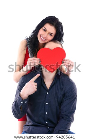 A beautiful young woman hides her face behind a guy with a big red heart - stock photo