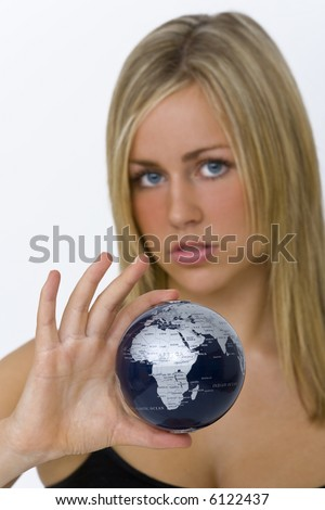 A beautiful young woman holding a globe in her hand, the focus is on the globe and Africa in particular.