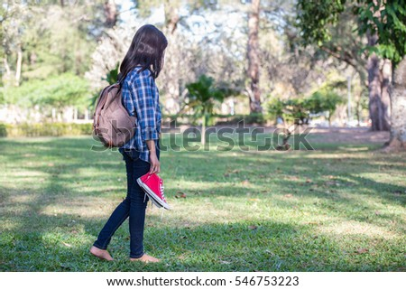 A beautiful young woman holding a red shoe. Walk in the park