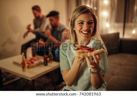 A beautiful young woman holding a slice of pizza in her hands.