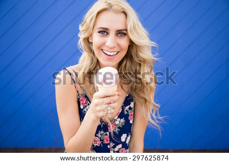 A beautiful young woman holding her strawberry ice cream cone in front of a bright blue wall. It is summertime and she looks happy. She has long blond hair and looks like a California beach girl. - stock photo