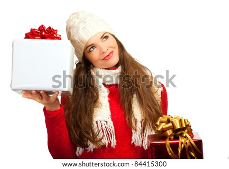 A beautiful young woman holding two Christmas gifts and looking contemplative.