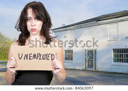 A beautiful young woman holding up a blank sign - stock photo