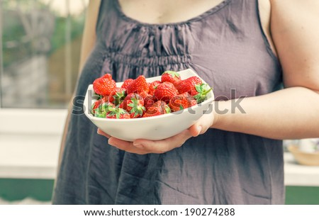 A beautiful young woman holding up a very large bowl of fresh strawberries. Gorgeous slender young brunette woman indoors part of the body shot - stock photo