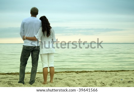 A beautiful young woman holds her handsome partner as they watch the sunset together on a romantic beach. - stock photo
