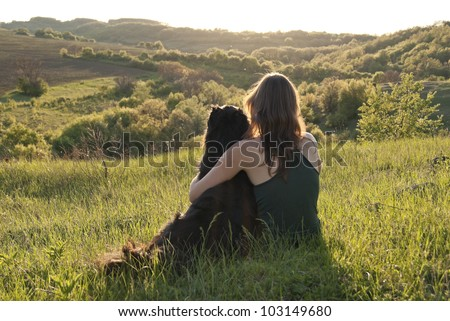 A beautiful young woman hugs her dog as they sit in a field - stock photo