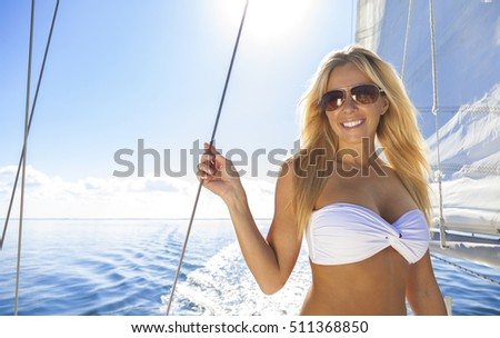 A beautiful young woman in a bikini and sunglasses standing a sail boat on a calm blue sea